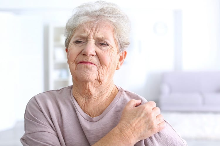 Elderly Woman Holding For Painful Shoulder