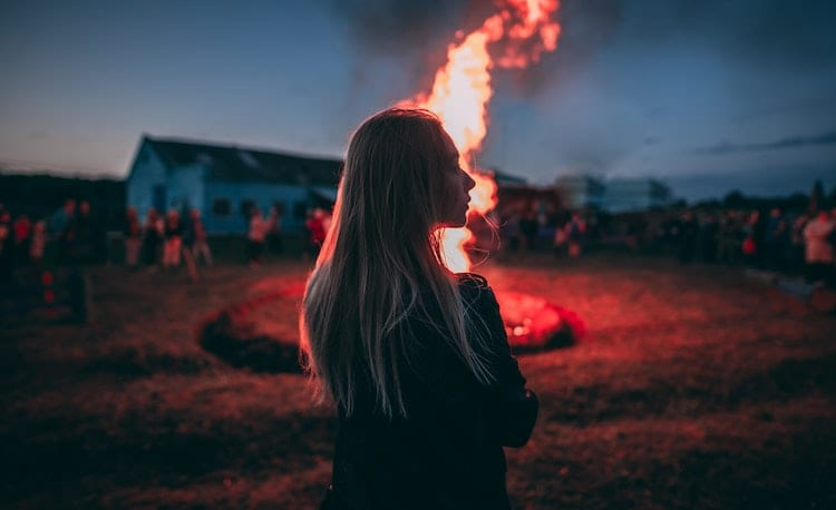 Woman standing on front of the bonfire.