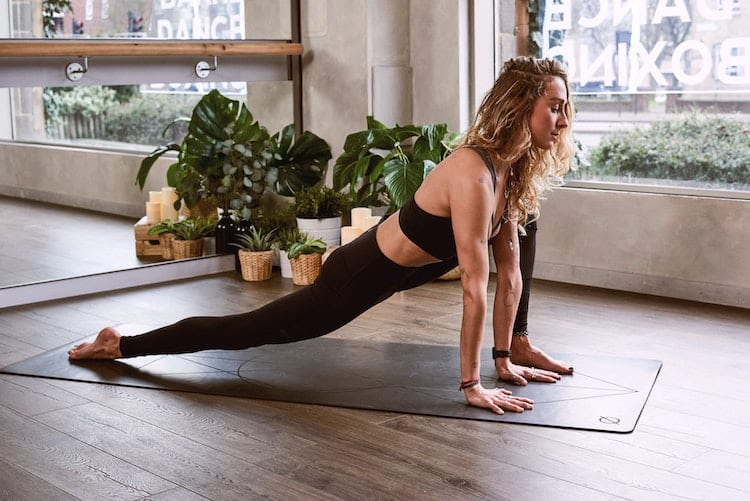 Woman is doing yoga near the window.